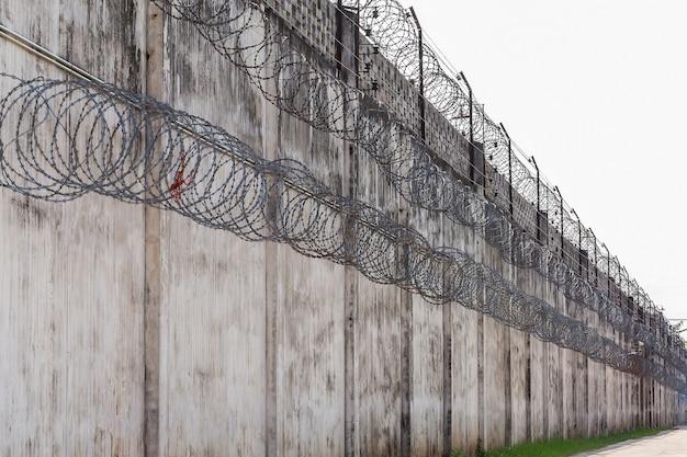 Ściany więzienia, ogrodzenie z drutu kolczastego.
