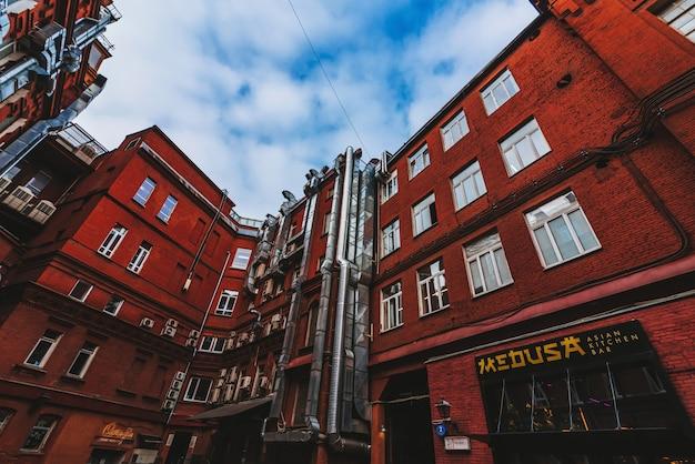 Ściany z czerwonej cegły starych budynków przemysłowych z rurami klimatyzacyjnymi i wentylacyjnymi
