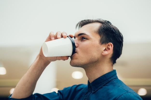 Ścieśniać. atrakcyjny młody mężczyzna z kawą na wynos