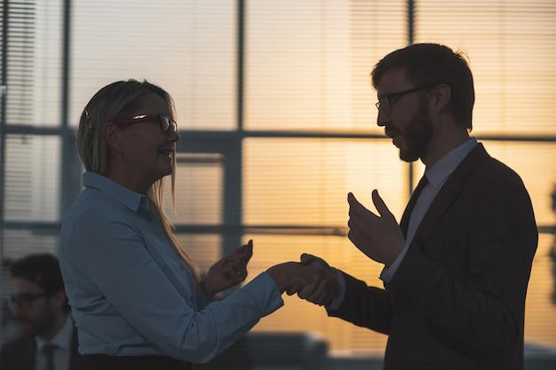 Ścieśniać. biznes dama uścisk dłoni z młodym pracownikiem. ludzie biznesu w rozproszeniu. kontury ludzi biznesu