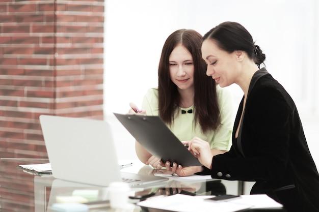 Ścieśniać. biznes kobieta robienie notatek siedząc na swoim biurku.