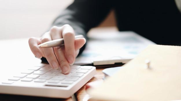 Ścieśniać biznes kobieta za pomocą kalkulatora i laptopa do finansów matematycznych na drewnianym biurku