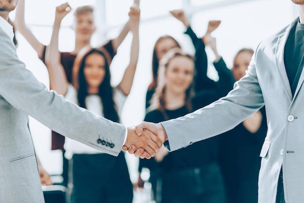 Ścieśniać. biznes uścisk dłoni na niewyraźne tło sali konferencyjnej