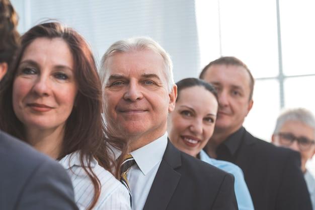 Ścieśniać. biznesmen dorosły stojący wśród swoich kolegów. pomysł na biznes