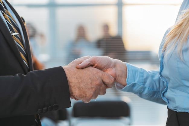 Ścieśniać. biznesmen grzecznie uścisk dłoni z kobietą biznesu. koncepcja współpracy