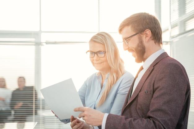 Ścieśniać. biznesmen i bizneswoman omawianie dokumentu biznesowego.