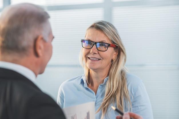Ścieśniać. biznesmen i bizneswoman rozmawia stojąc w biurze. pomysł na biznes