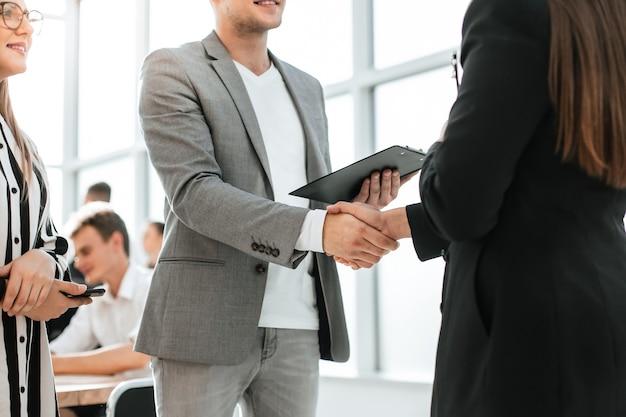 Ścieśniać. biznesmen i bizneswoman uścisk dłoni ze sobą. koncepcja współpracy