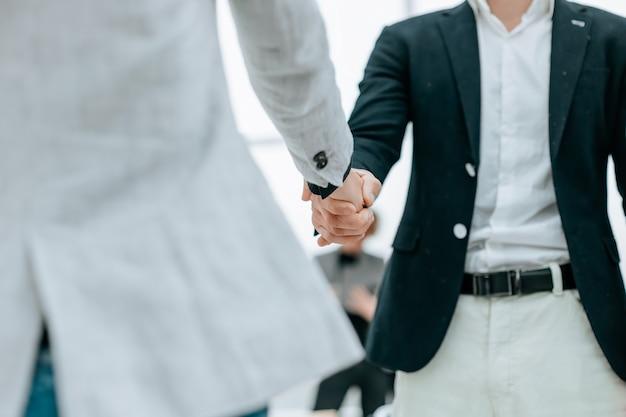 Ścieśniać. biznesmen i bizneswoman witają się uściskiem dłoni. koncepcja współpracy