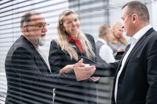 Ścieśniać. biznesmen i businesswoman uścisk dłoni stojąc w holu urzędu. koncepcja współpracy