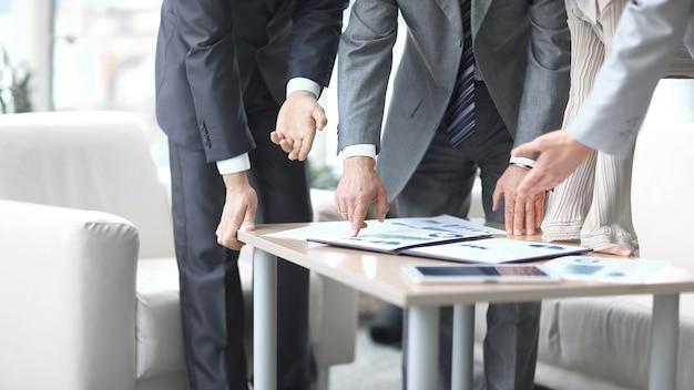 Ścieśniać. biznesmen, omawiając z kolegami dane finansowe.