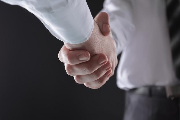 Ścieśniać. biznesmen uścisk dłoni z partnerem biznesowym. na białym tle na czarnym tle