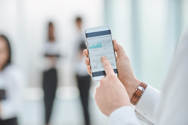 Ścieśniać. biznesmen używa swojego smartfona do sprawdzania informacji finansowych. ludzie i technologia