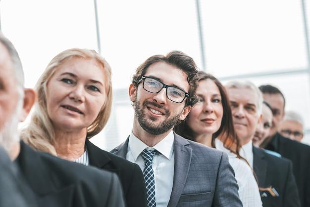 Ścieśniać. dorosła kobieta biznesu stojąca w rzędzie swoich kolegów. pomysł na biznes