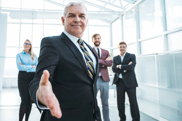 Ścieśniać. dorosły biznesmen pewnie wyciągając rękę do uścisku dłoni.
