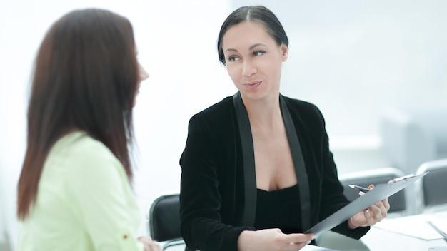 Ścieśniać. dwie kobiety biznesu omawiające dokumenty
