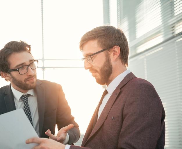 Ścieśniać. dwóch biznesmenów omawiających dokument biznesowy. dni pracy biurowej.