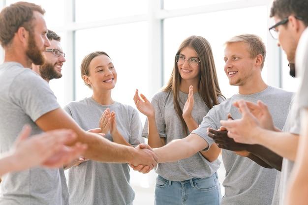 Ścieśniać. dwóch liderów młodzieżowych ściskających dłonie. biznes i edukacja