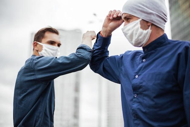 Ścieśniać. dwóch młodych mężczyzn witających się łokciami. pojęcie ochrony zdrowia