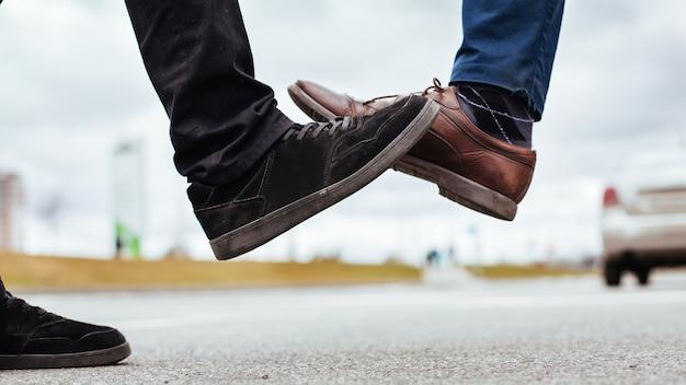 Ścieśniać. dwóch młodych mężczyzn witających się na ulicy miasta. pojęcie ochrony zdrowia