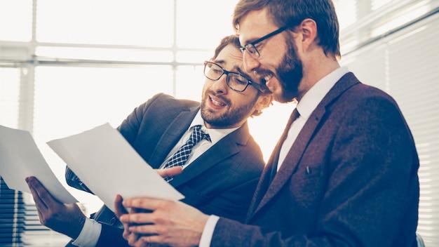 Ścieśniać. dwóch pracowników omawiających dokumenty biznesowe. dni pracy biurowej.