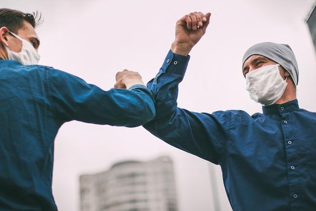 Ścieśniać. dwóch przyjaciół witających się łokciami na miejskiej ulicy. pojęcie ochrony zdrowia