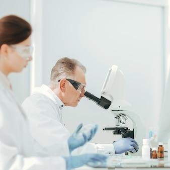 Ścieśniać. farmaceutów z całego świata przy użyciu mikroskopu w laboratorium.