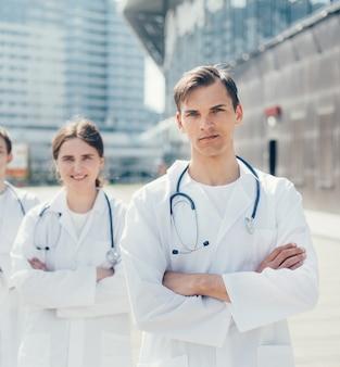 Ścieśniać. grupa lekarzy stojących na ulicy miasta. pojęcie ochrony zdrowia.