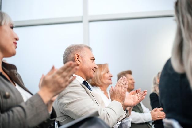 Ścieśniać. grupa ludzi biznesu bije brawo podczas seminarium biznesowego. biznes i edukacja