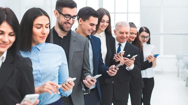 Ścieśniać. grupa ludzi biznesu stojących w rzędzie ze smartfonami