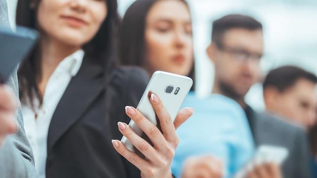 Ścieśniać. grupa młodych biznesmenów czytających wiadomości na swoich smartfonach