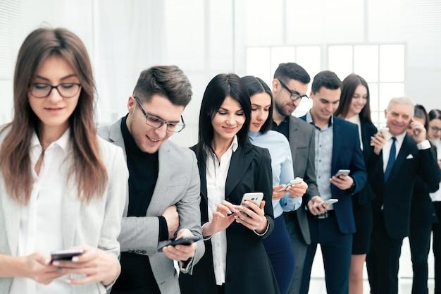 Ścieśniać. grupa młodych ludzi czytająca wiadomości na swoich smartfonach
