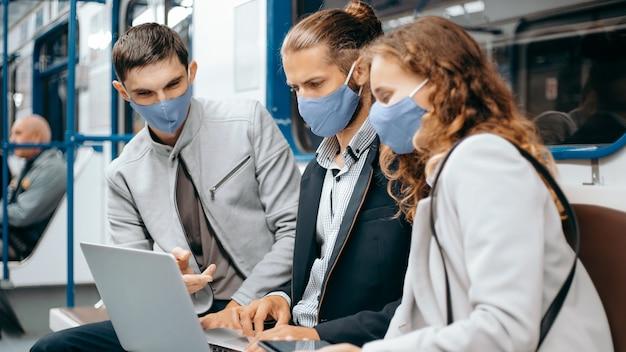 Ścieśniać. grupa młodych ludzi korzystających z laptopa siedząc w wagonie metra.