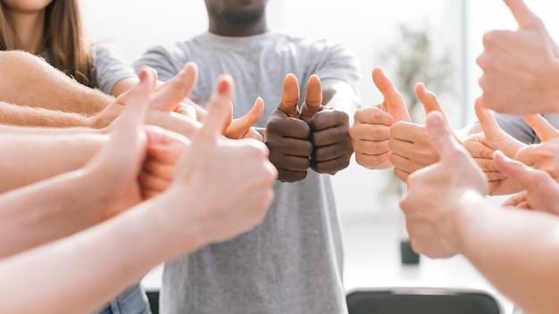 Ścieśniać. grupa młodych ludzi pokazując kciuki do góry. koncepcja sukcesu