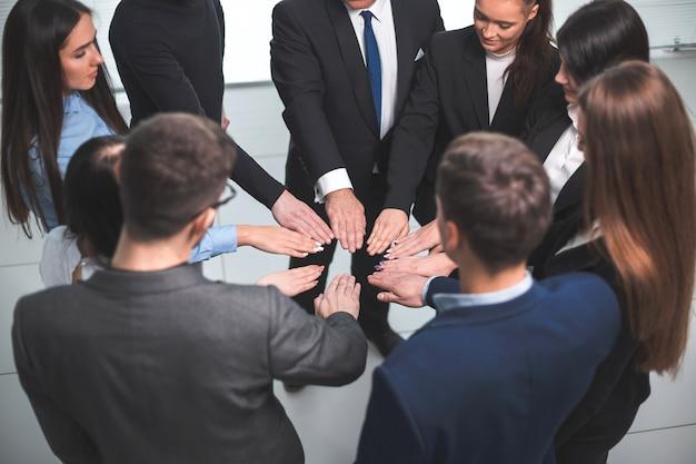 Ścieśniać. grupa młodych pracowników stojących w kręgu. pojęcie pracy zespołowej