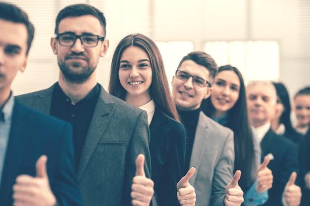 Ścieśniać. grupa młodych przedsiębiorców stojących razem i pokazujących kciuki w górę