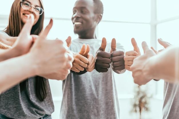 Ścieśniać. grupa młodzieży stojącej w kręgu i pokazującej kciuk do góry