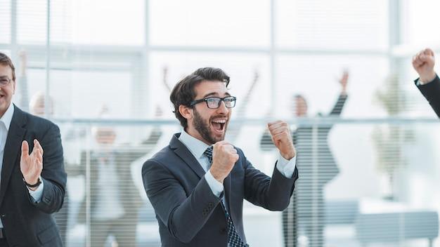 Ścieśniać. grupa odnoszących sukcesy pracowników świętuje w biurze.
