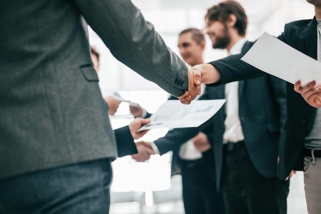 Ścieśniać. grupa pracowników ściskających dłonie na spotkaniu w biurze. pomysł na biznes