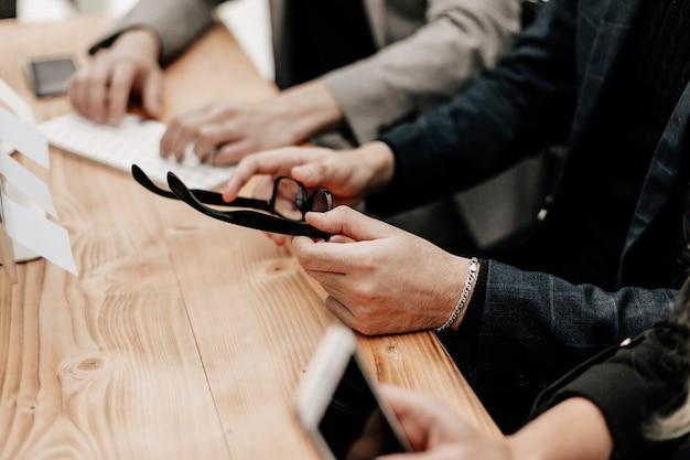 Ścieśniać. grupa robocza siedzi przy biurku. ludzie i technologia