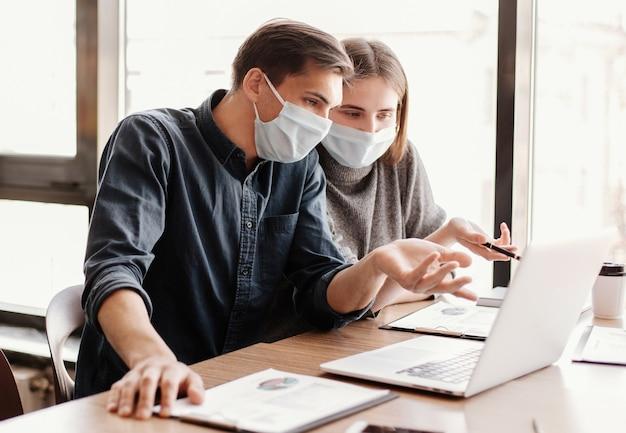 Ścieśniać. grupa robocza w maskach ochronnych omawiająca dane finansowe.