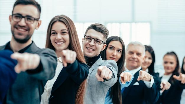 Ścieśniać. grupa różnorodnych ludzi biznesu wskazujących do przodu
