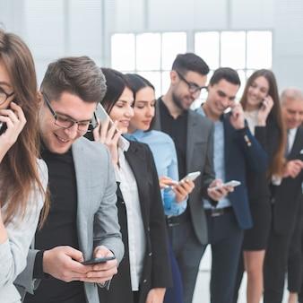 Ścieśniać. grupa różnorodnych młodych ludzi korzysta ze swoich smartfonów