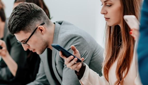 Ścieśniać. grupa różnorodnych młodych ludzi patrząca na ekrany swoich smartfonów