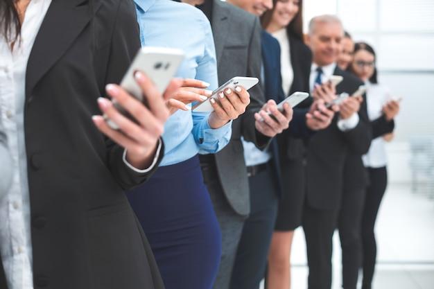 Ścieśniać. grupa różnorodnych pracowników ze smartfonami stojącymi w rzędzie