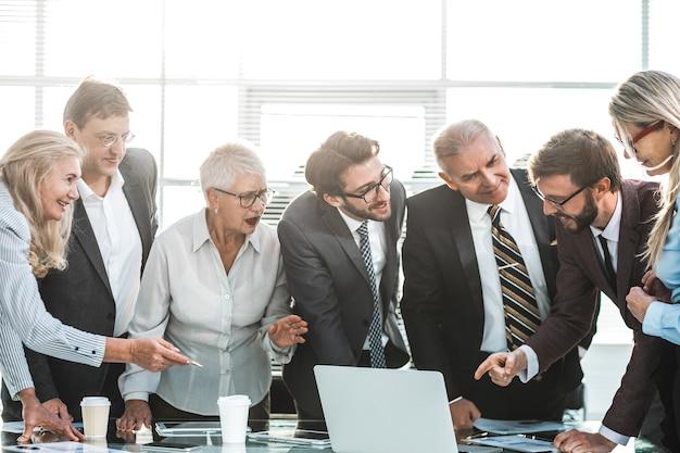 Ścieśniać. grupa różnorodnych specjalistów patrzących na ekran laptopa. pomysł na biznes