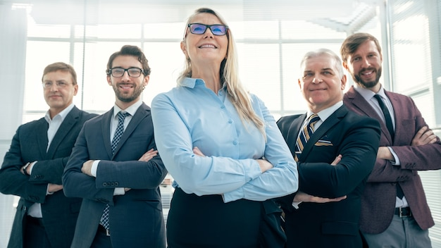 Ścieśniać. grupa szczęśliwych ludzi biznesu stojących w biurze