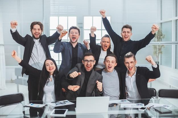 Ścieśniać. grupa szczęśliwych pracowników siedzi w biurze desk. pojęcie pracy zespołowej