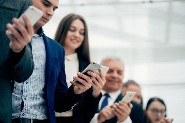 Ścieśniać. grupa uśmiechniętych ludzi biznesu, patrząc na ekrany swoich smartfonów