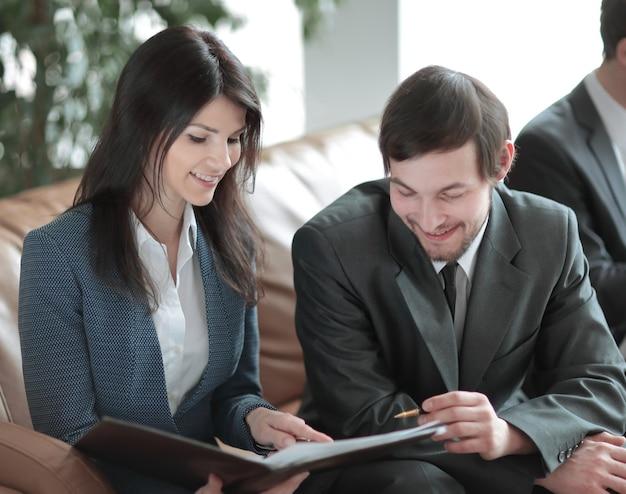 Ścieśniać. kierownik i klient do omówienia dokumentów w nowoczesnym biurze